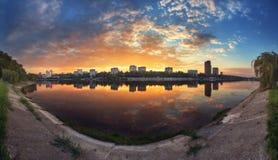 Sommarsolnedgång i staden Reflexion på floden Royaltyfria Bilder