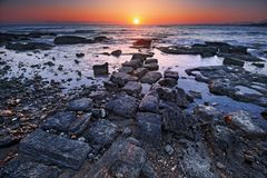 Sommarsolnedgång på den steniga stranden i forntida stad av sidan i Antalya Royaltyfria Bilder