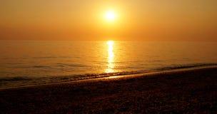 Sommarsolnedgång på en havsstrand Arkivfoton