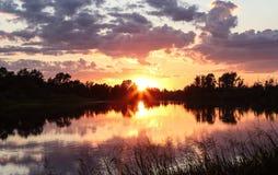 Sommarsolnedgång på sjön Arkivfoton