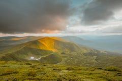 Sommarsoluppgång i bergen Arkivbild