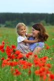 Sommarstående av den lyckliga kela modern och dottern i vallmofältet arkivbild