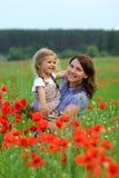 Sommarstående av den lyckliga kela modern och dottern i vallmofältet arkivbilder