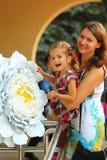 Sommarstående av en lycklig le moder och dotter i festlig kläder med blommor fotografering för bildbyråer