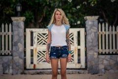 Sommarstående av en ung bedöva blond flicka Bär kortslutningar för en vit tshirt och grov bomullstvill Utomhus livsstil, mode royaltyfri fotografi
