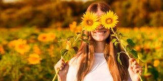 Sommarst?ende Lycklig glad flicka med solrosen som tycker om naturen och att skratta royaltyfria foton