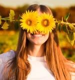 Sommarst?ende Lycklig glad flicka med solrosen som tycker om naturen och att skratta royaltyfri bild