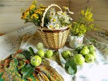 Sommarstilleben som göras av vide- korg, lösa blommor och gröna äpplen Royaltyfria Foton