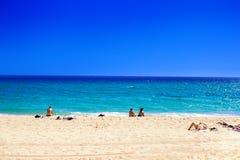 Sommarstrand med folk som tar sunbath på guld- sand Inte galande Arkivfoto