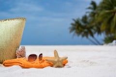 Sommarstrandpåse med korall, handduken, solglasögon och korall på den sandiga stranden Arkivbilder