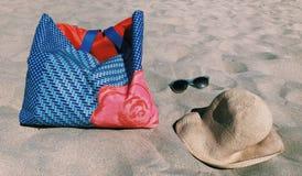 Sommarstrandpåse, solglasögon och Straw Hat på sanden arkivfoto