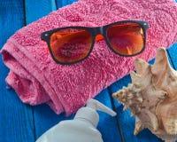Sommarstrandtillbehör på en blå trätabell Handduk solglasögon, skal, sunblock Begreppet av en semesterort på stranden Arkivbilder