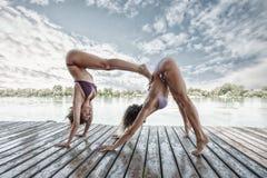 Sommartidyogapar av kvinnor som gör yoga på flodflotten Royaltyfri Bild