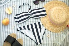 Sommartillbehör på stranden, baddräkten, hatten och exponeringsglasen arkivbild