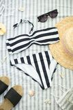 Sommartillbehör på stranden, baddräkten, hatten och exponeringsglasen royaltyfri fotografi