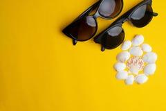 Sommartillbehör, skal och parsolexponeringsglas på gul bakgrund Sommarsemester, honungmåne och havsbegrepp royaltyfria foton