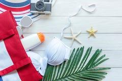 Sommartillbehören, den vita bikinin, kamera går till semestern för ferie för loppplanet i stranden tropiskt hav Ovanlig b?sta sik royaltyfri bild