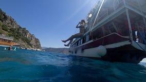 Sommarturism, ung kvinna i baddräktbanhoppning från det motoriska skeppet som slösar det klara havet och att göra mycket av plask arkivfilmer