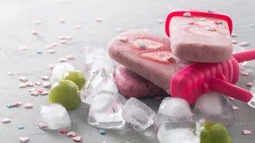 Sommarvärme: uppfriskande rosa färgfruktglass med jordgubbestycken som omges av genomskinliga och gröna iskuber på a Royaltyfri Bild