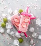 Sommarvärme: uppfriskande rosa färgfruktis med jordgubbestycken som omges av genomskinliga och gröna iskuber på en grå tabell Arkivfoton