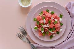 Sommarvattenmelonsallad med fetaost, sesamfrö och mintkaramellsidor på rosa färgplattan Royaltyfria Bilder