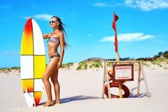 Sommarvattensportar Sätta på land semestern surfa Kvinna i bikini Arkivbild