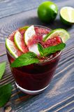 Sommarvitamindrinken från körsbäret, limefrukt, is, dekorerade med mintkaramellsidor på en trätabell royaltyfria foton