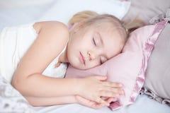 Sommeil adorable en gros plan de petite fille dans le lit avec les yeux fermés Image stock