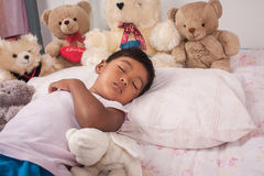 Sommeil asiatique de garçon avec l'ours de nounours Photo stock