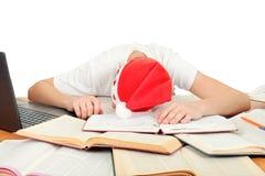 Sommeil d'étudiant dans le chapeau de Santa Photographie stock