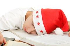 Sommeil d'étudiant dans le chapeau de Santa Image stock