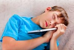 Sommeil d'adolescent avec une Tablette photo stock