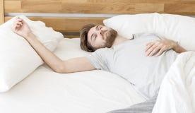 Sommeil d'hommes sur le lit Photographie stock libre de droits