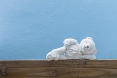 Sommeil d'ours de nounours, sur le vieux bois et le fond bleu de mur Photographie stock