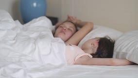 Sommeil de deux soeurs pendant le matin dans le lit banque de vidéos