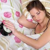 Sommeil de femme dans le bâti avec l'alarme Photos stock