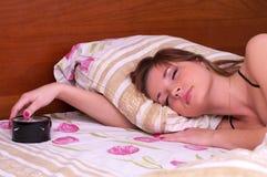 Sommeil de femme dans le bâti avec l'alarme Image stock