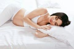 Sommeil de femme enceinte Fille dormant avec l'oreiller sur le lit photographie stock libre de droits