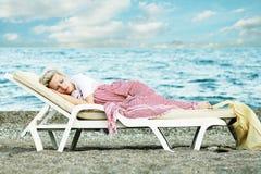 Sommeil de femme sur la plage Image stock