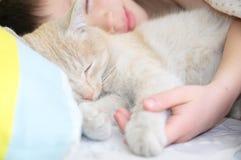 Sommeil de garçon avec le chat, l'animal familier préféré se trouvant sur le coffre d'enfant, les interactions entre les enfants  Photos stock