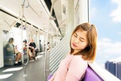 Sommeil de jeune femme tout en prenant le train de ciel Photographie stock libre de droits