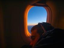 Sommeil de jeune homme dans l'avion photo stock
