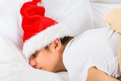Sommeil de jeune homme en Santa Hat photo stock