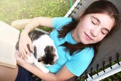 Sommeil de l'adolescence de fille dans le salon de cabriolet avec le chat Images libres de droits