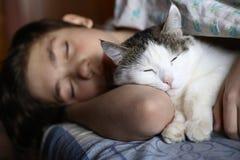 Sommeil de l'adolescence de garçon avec le chat dans l'étreinte de lit Photographie stock