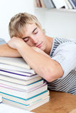 Sommeil de l'adolescence fatigué dans une bibliothèque Photographie stock