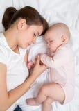 Sommeil de mère et de bébé dans le lit ensemble images stock