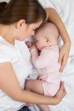 Sommeil de mère et de bébé dans le lit La maman embrasse sa petite fille photo stock