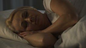 Sommeil de sourire de femme d'une cinquantaine d'années avec le sommeil sain, le calme se sentant et le bonheur banque de vidéos