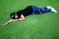 Sommeil fatigué de fille sur l'herbe dans le jardin Photographie stock libre de droits